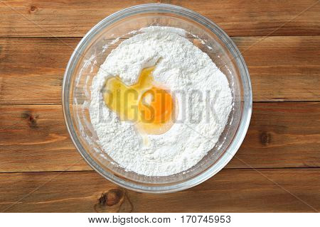 Glass bowl with flour and egg on wooden background