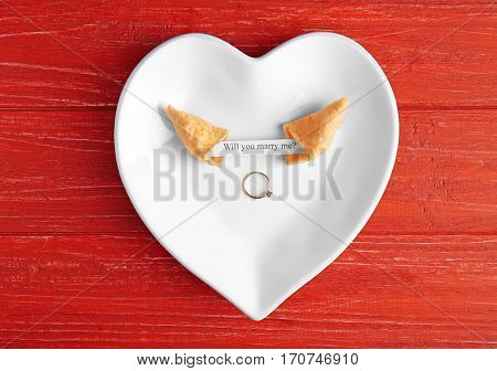 Fortune cookie with golden ring on wooden background