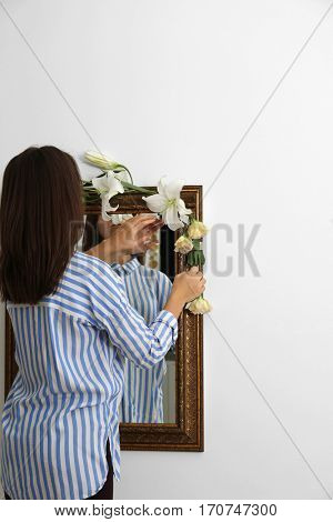 Young woman decorating vintage mirror with flowers