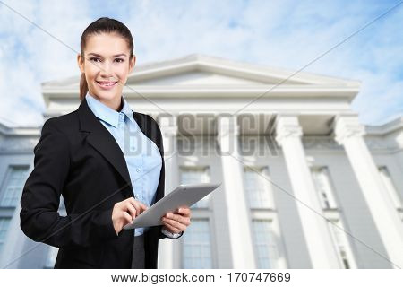 Law and justice concept. Young woman with tablet on courthouse background