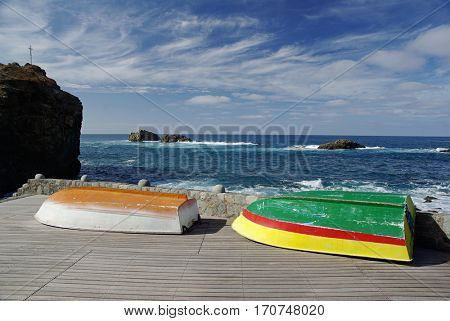 Two flipped colorful boats on the seashore side. Tenerife, Canary island, Spain
