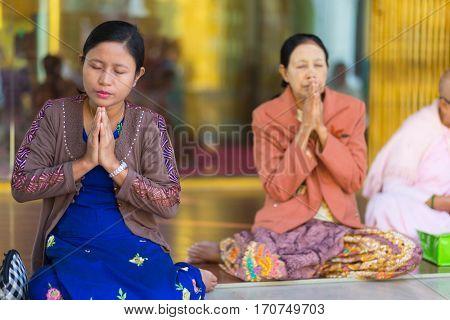 RANGOON, MYANMAR - JANUARY 18, 2017 : Women are praying Buddha at the Shwedagon pagoda in Rangoon (Yangon), Myanmar