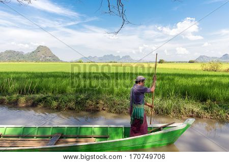 HPA-AN, MYANMAR - JANUARY 20, 2017 : A boatman, is sailing a wooden boat in the rice field river in Hpa-An, Myanmar