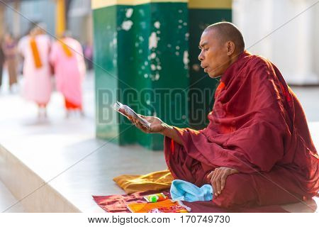 RANGOON, MYANMAR - JANUARY 18, 2017 : A Burmese monk is reading and chanting sacred Buddhism writings at the Shwedagon pagoda in Rangoon (Yangon), Myanmar