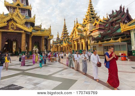 RANGOON, MYANMAR - JANUARY 18, 2017 : Burmese people and monks are walking in line for praying Buddha at the Shwedagon pagoda in Rangoon (Yangon), Myanmar