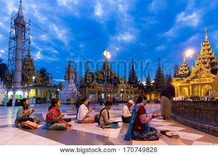 RANGOON, MYANMAR - JANUARY 18, 2017 : Burmese people sitting and praying Buddha at the Shwedagon pagoda early morning in Rangoon (Yangon), Myanmar