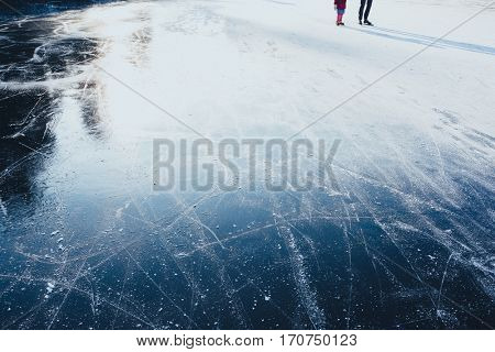 Surface of outdoor ice with skaters, replete with skate marks. Ice background