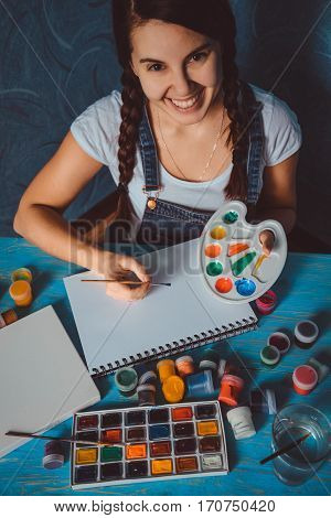 young smiling woman drawing with paint in white sheet