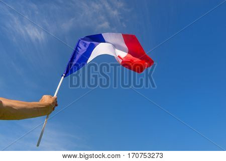 Little French flag in hand against blue sky