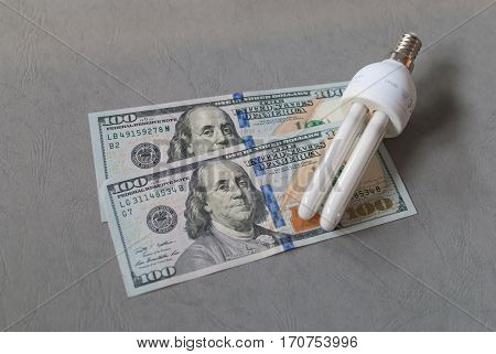 Energy saver light bulb laid on two 100 dollar bills on a grey surface, isolated close up, economy and saving concept