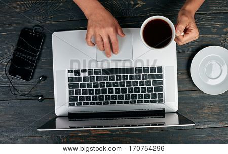 Woman working on her laptop computer. Wooden background, smartphone and cup of coffee. Top view