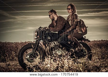 Young, stylish cafe racer couple on vintage custom motorcycles in field.