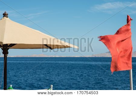 red flag at sea. Swimming is prohibited at the sea