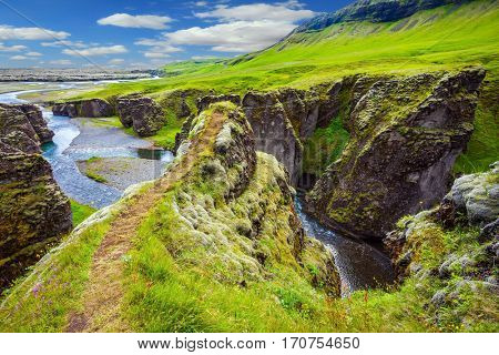 Vertical huge rocks surround the stream with glacial water. The concept of active northern tourism.  The striking canyon in Iceland. The Icelandic tundra in July