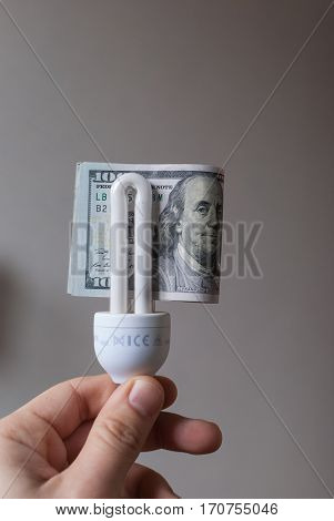 Man's hand holding energy saver light bulb with 100 dollar bill folded through, isolated close up, economy and saving concept