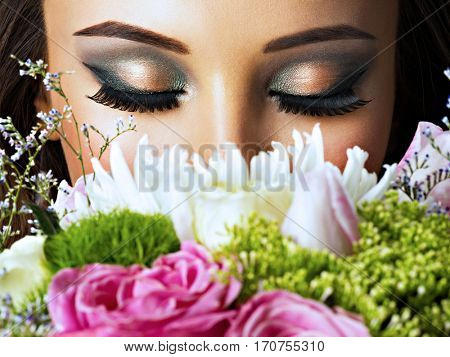 Closeup face of beautiful  girl with flowers. Young attractive woman holds the bouquet of spring flowers