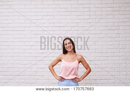 Mid shot portrait of pretty woman. Wearing trendy clothes. Posing with hands on hips isolated over white background