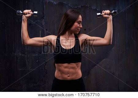 Close-up of active sportive athletic woman looking at bicep while pumping up dumbbells. Biceps concept. Fitness sport training lifestyle