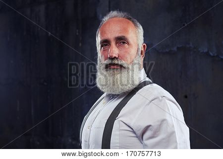 Close-up of serious gaze of mature man looking directly at the camera isolated over black background. He seemed preoccupied by something