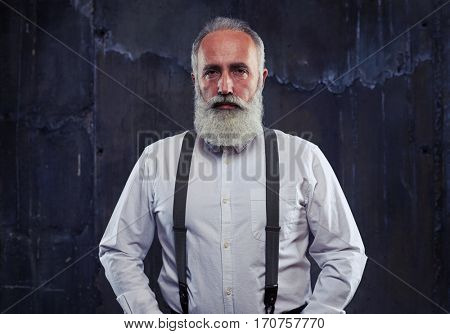 Close-up of serious Caucasian gray bearded man standing in studio isolated over black background. Male wearing formal wear with suspenders