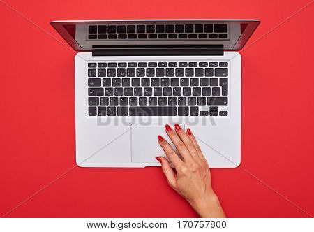 High angle of hand touching touchpad on the silver laptop isolated over red flat layout
