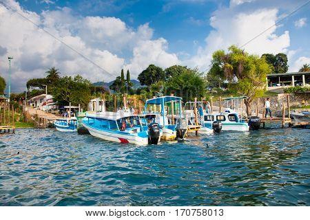 PANAJACHEL, GUATEMALA-DEC 23, 2015: People board the boat at the dock of Lake Atitlan in Panajachel, Guatemala. Central America.