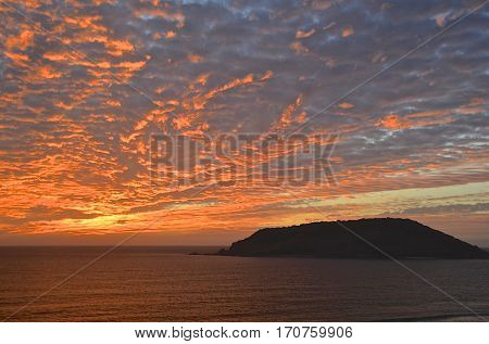 Beautiful fiery red sunset over a tropical sea  and island