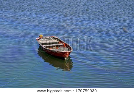 A solitary red fishing boat in the deep blue water.