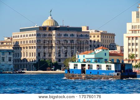 HAVANA,CUBA - FEBRUARY 7,2017 : An old motorboat carries passengers across the bay of Havana with colorful buildings on the background