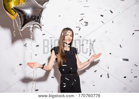 young woman holding star balloon with fly confetti on party over white background