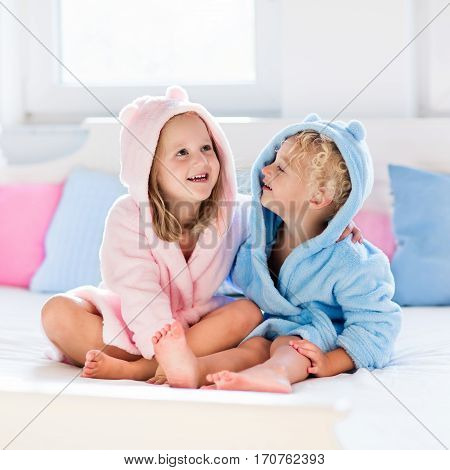 Happy laughing kids boy and girl in soft bathrobe after bath play on white bed with blue and pink pillows in sunny bedroom. Child in clean and dry towel. Wash infant hygiene health and skin care.