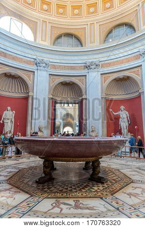 VATICAN, ITALY - Circa May, 2016: Hercules statue figure and round monolithic porphyry basin in Round Room of Pio-Clementino Museum in Vatican museums in Vatican city