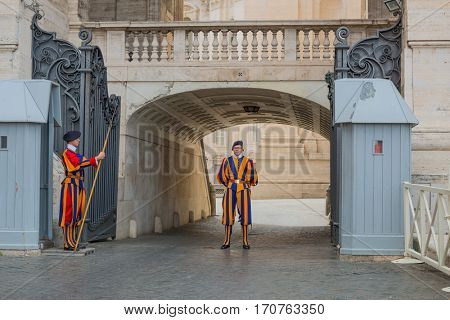 VATICAN CITY, VATICAN - MAY 19, 2016: A pair of Papal Swiss guards in their traditional uniforms stand guard at the entrance of Saint Peter's Basilica on May 19, 2016.