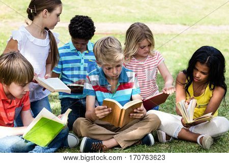 Children reading book in the park on a sunny day