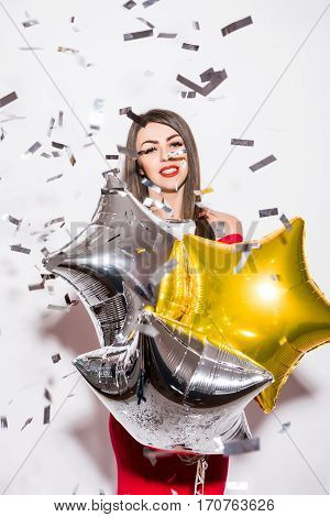 Young woman in red dress holding star balloon with fly confetti at party over white background