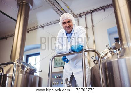 Low angle portrait of manufacturer leaning on pipe at brewery