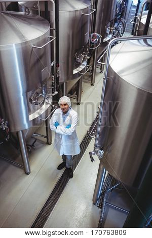 High angle view of smiling manufacturer standing amidst storage tanks at brewery