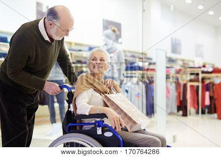 Senior caregiver taking his disabled wife to go shopping