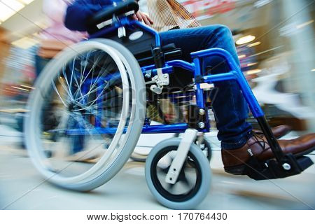Invalid man in wheel-chair being pushed by caregiver
