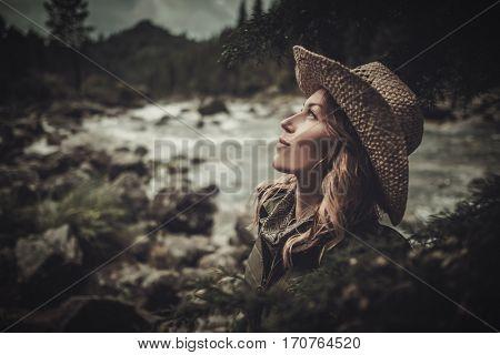 Beautiful woman hiker near wild mountain river
