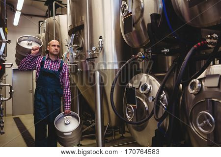 Brewery worker carrying kegs at factory
