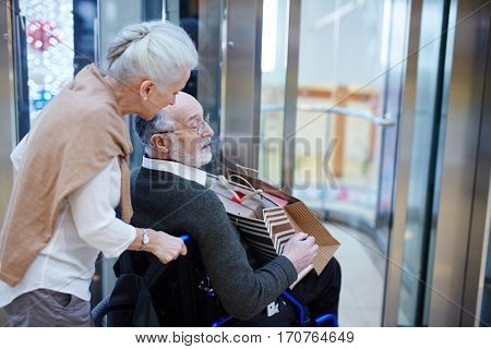 Senior woman taking care of her disabled husband during shopping