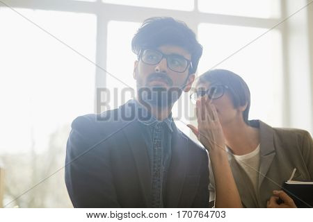 Portrait of two office workers gossiping about newcomer: young woman leaning in to whisper to mans ear as they both looking judgingly at someone