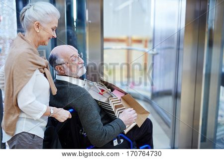 Senior spouses entering modern shopping-center