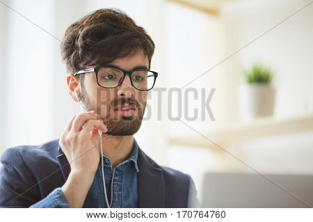Portrait of young creative man wearing glasses focused while holding videochat interview applying for job position using hands free mic and laptop at modern workplace
