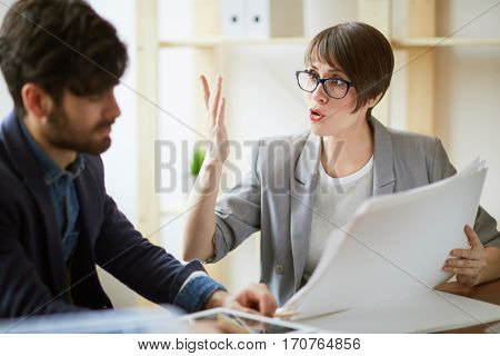 Portrait of two successful business people communicating in office, energetic woman gesturing actively while explaining work plans and documentation details to colleague