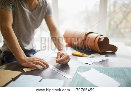 Closeup portrait of unrecognizable leather craftsman working making measupenets in patterns at table in workshop studio