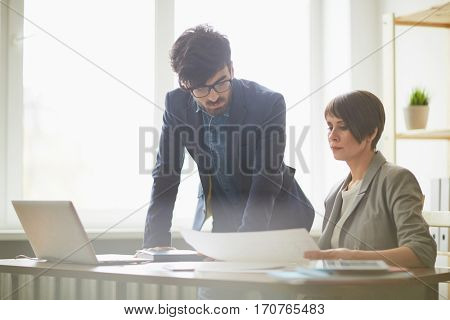 Portrait of modern male supervisor giving instructions to employee leaning on her desk and looking at documentation in light office