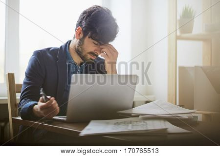 Portrait of exhausted young man sitting at workplace in modern office against window rubbing his forehead and closing eyes in pain while working at laptop