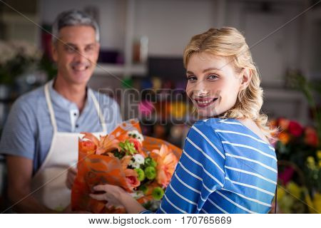 Florist giving bouquet of flower to customer in the shop